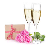 Two champagne glasses, gift box and pink rose flowers Stock Images