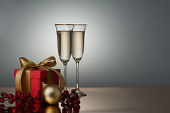Two champagne glasses on a golden surface Stock Photos