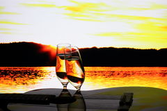 Two champagne glasses with guitar at sunset Stock Photo