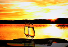 Two champagne glasses with guitar at sunset Royalty Free Stock Image