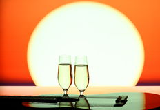 Two champagne glasses with guitar at sunset Royalty Free Stock Photography