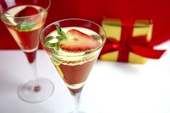 Two champagne glasses with heart shaped strawberry and a gift in the background Valentine`s Day concept royalty free stock image