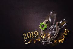 Two champagne glasses with a horseshoe and shamrock as lucky charm stock photography
