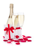 Two champagne glasses, letter and rose petals Royalty Free Stock Image