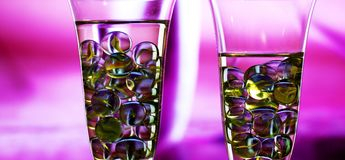 Two champagne glasses with marbles. concept. Two champagne glasses with marbles against blurred abstract background. Abstract reflections on marbles.Purple Stock Images