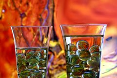 Two champagne glasses with marbles. Filled with drink. Two champagne glasses with marbles against red blurred abstract background. Abstract reflections on Royalty Free Stock Photo