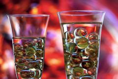 Two champagne glasses with marbles. Drink concept. Two champagne glasses with marbles against red blurred abstract background. Abstract reflections on marbles Stock Image