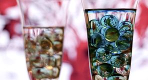 Two champagne glasses with marbles. left glass in focus. Two champagne glasses with marbles against red and whiteblurred abstract background. Abstract blue Stock Photography