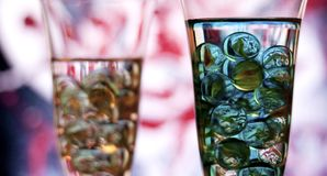 Two champagne glasses with marbles. Right glass in focus. Two champagne glasses with marbles against red and white blurred abstract background. Abstract blue Stock Images
