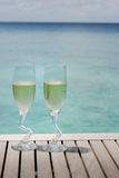 Two champagne glasses by the ocean Stock Photography