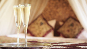 Two champagne glasses with oriental canopy bed at the background Stock Image