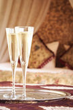 Two champagne glasses with oriental canopy bed at the background Stock Photography