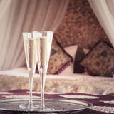 Two champagne glasses with oriental canopy bed at the background Royalty Free Stock Photography