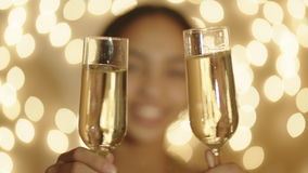 Two champagne glasses and out of focus female portrait on the background. Close up shot of two champagne glasses in female hands. Woman portrait and bokeh lights stock video footage