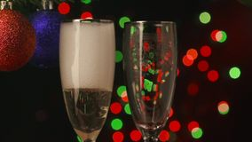 Two champagne glasses with pouring champagne ready. Two champagne glasses ready to bring in the New Year stock footage