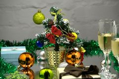Two champagne glasses, red Merry Christmas ball hanging on fir branch under snow and fir-cones over colorful blurred illumination,. Card for new year greeting Royalty Free Stock Images