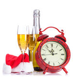 Two champagne glasses, santa hat, bottle and clock Stock Photo