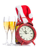 Two champagne glasses, santa hat, bottle and clock Royalty Free Stock Photography