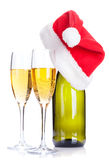 Two champagne glasses and santa hat over bottle Royalty Free Stock Images