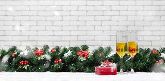 Two champagne glasses setting next to a red gift box on snowy ta stock photo