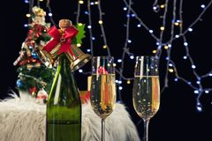 Two champagne glasses and sparkle, Christmas holiday background. With decorated christmas tree, santa claus and gift boxes on black background and christmas Stock Image