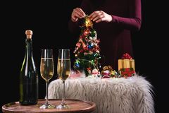 Two champagne glasses and sparkle, Christmas holiday background. With decorated christmas tree, santa claus and gift boxes on black background and christmas Stock Photos