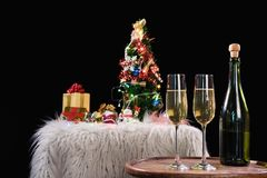 Two champagne glasses and sparkle, Christmas holiday background. With decorated christmas tree, santa claus and gift boxes on black background and christmas Royalty Free Stock Images