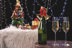 Two champagne glasses and sparkle, Christmas holiday background. With decorated christmas tree, santa claus and gift boxes on black background and christmas Royalty Free Stock Image