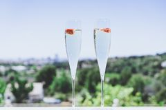 Two champagne glasses with strawberry on sunny terrace outdoor patio overlooking clean blue sky at summer day outside of. The city stock photos
