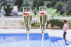 Two champagne glasses with strawberry on sunny terrace outdoor patio overlooking swimming pool at summer day outside of stock photo