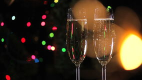 Two champagne glasses. For Title. Christmas decorations. In the foreground is blurred sparkler stock video footage
