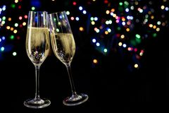 Two champagne glasses toast against a dark background with color royalty free stock photo