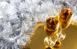 Two champagne or wine glasses with gold and silver christmas tinsel decoration. royalty free stock photos