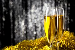 Two champagne or wine glasses with gold and silver christmas tinsel decoration. stock image