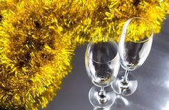 Two champagne or wine glasses with gold and silver christmas tinsel decoration. royalty free stock photo