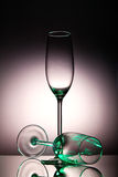 Two champaigne glasses. With a green tint on a shiny surface Stock Photos