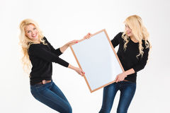 Two charming blonde sisters twins having fun holding blank board Royalty Free Stock Images