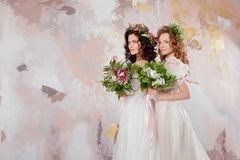 Two charming brides in beautiful spring wreaths on their heads. Beautiful young women in wedding dresses. Studio portrait stock photo