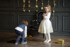 Two charming children rejoice to Christmas gifts. Royalty Free Stock Photos