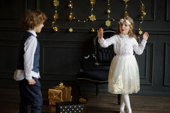 Two charming children rejoice to Christmas gifts. Royalty Free Stock Photography