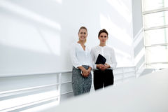 Two charming female in formal wear posing for the camera against white wall background with copy space area Royalty Free Stock Photography