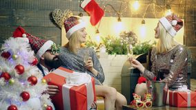 Two charming girls and a bearded man celebrate Christmas. Girls and bearded men drink champagne on the background of New. Year`s scenery. Concept of new year stock video