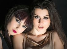 Two charming girls on a black background Stock Photography