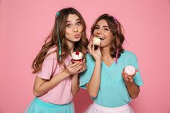 Two charming girls in colorful clothes enjoying tasty cupcakes,. Looking at camera isolated on pink background Stock Image