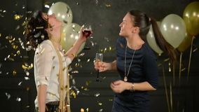 Two Charming Girls are Dancing Surrounded by the Confetti on Black Background with Balloons. One Lady with Curly Hair is. Two Charming Girls are Dancing stock footage