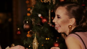 Two charming girls dress up Christmas tree. Holidays and jewelry concept - beautiful woman over christmas lights background stock footage