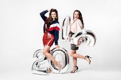 Two charming girls dressed in a stylish smart clothes are holding balloons in the shape of numbers 2019 on a white royalty free stock images