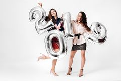 Two charming girls dressed in a stylish smart clothes are holding balloons in the shape of numbers 2019 on a white royalty free stock photography