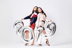 Two charming girls dressed in a stylish smart clothes are holding balloons in the shape of numbers 2019 on a white stock photography