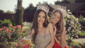 Two charming girls in evening gowns and crowns. Laughing and doing phone selfie in garden with roses stock video footage